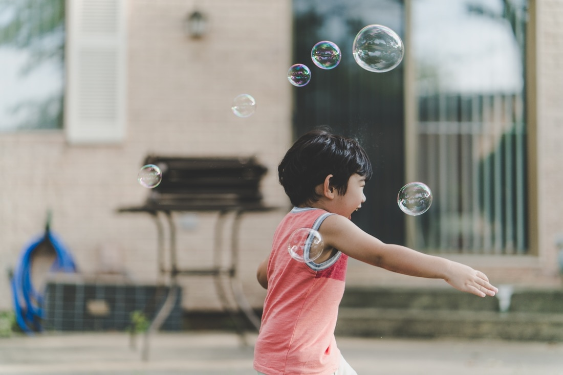 Boy running and having fun with bubbles. It is possible to overcome anxiety with the right therapy tools.