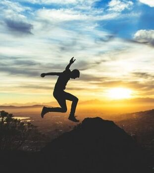 Man jumping over mountains. CBT can help you manage anxiety and OCD.