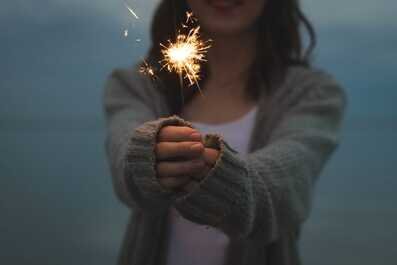 Woman holding sparkler at night. With the right therapy tools, you can overcome anxiety and OCD.